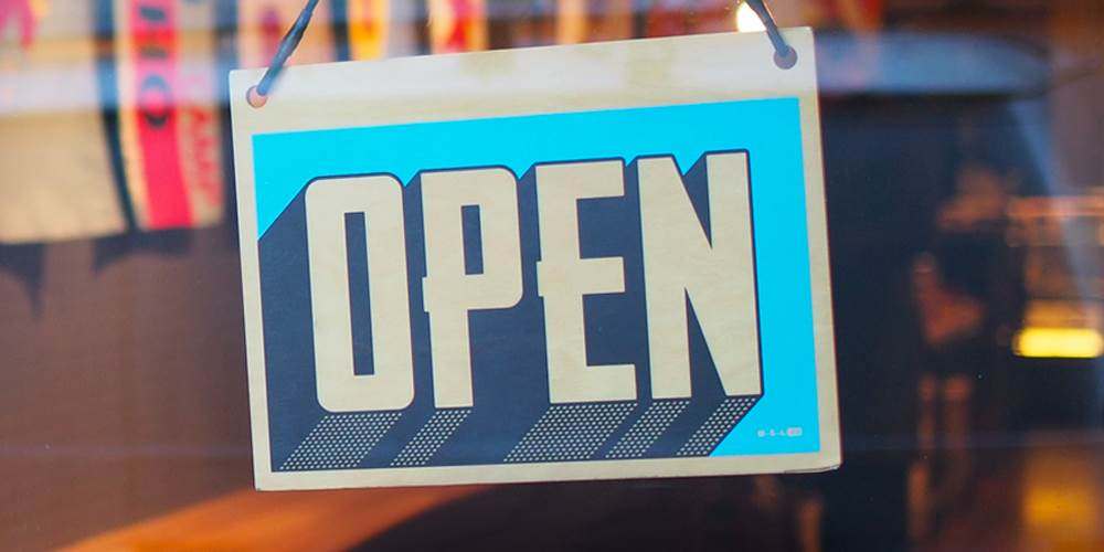 "An ""open"" sign hangs in a storefront window"
